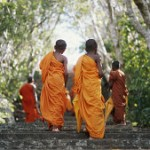 Young male monks (7-9) walking up steps outdoors, rear view